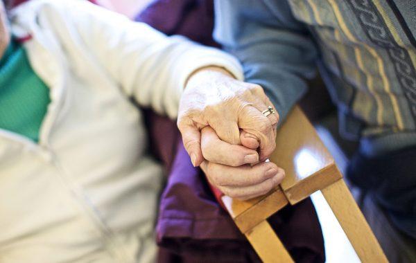 An elderly couple hold hands