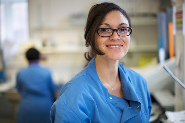 A woman in a blue uniform, at a workbench in a laboratory, smiling