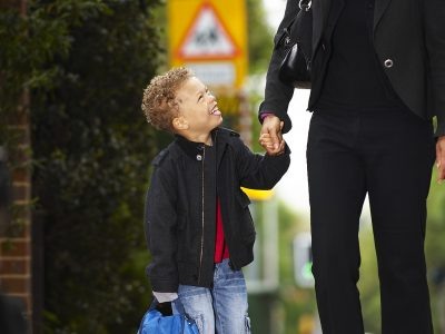A child and an adult walking along a pavement
