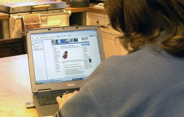 A woman using her laptop to look at NHS Direct website