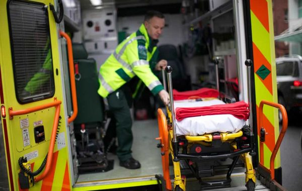 An empty trolley is wheeled onto an ambulance