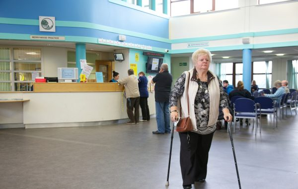 An older woman walking with sticks in a GP waiting area