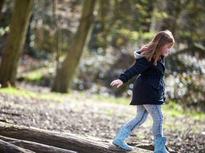 A young girl balances along a log. Image credit: World Obesity Federation