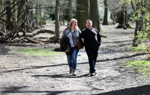 A couple walking in a wood. Image credit: World Obesity Federation