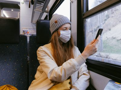 A young woman wearing a face mask and using a mobile phone on a train