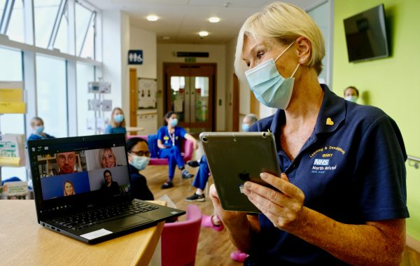 An NHS worker in a face mask during an online meeting