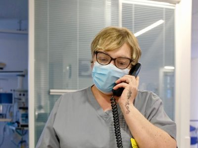 An NHS worker in a face mask on a phone call