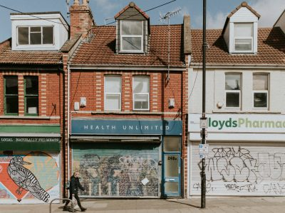 A woman walks down an empty street in Bristol with boarded up shops during the COVID-19 pandemic