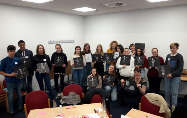 Young people holding up pictures of skeletons