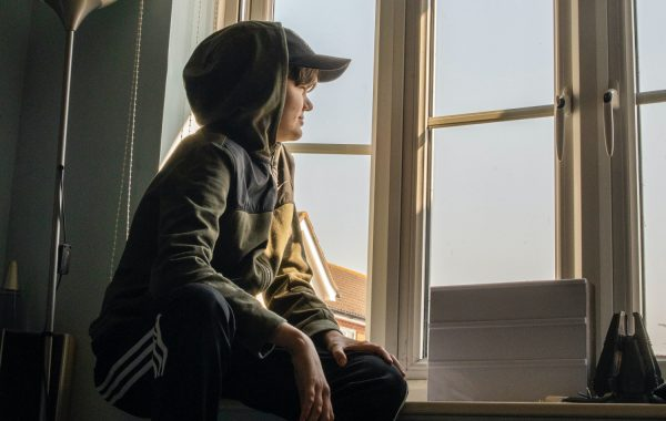 A young person looks out of a window