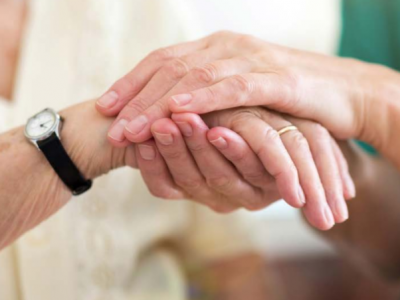An older person's hand being held by a carer
