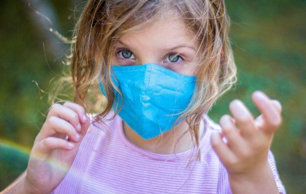 A little girl wearing a facemask