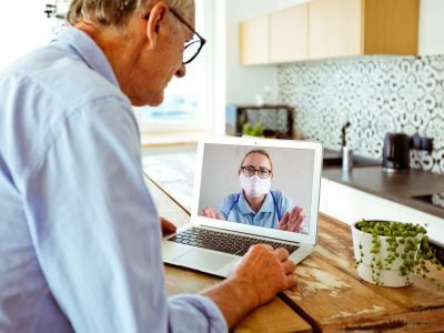 An older man has a video call with a clinician who is wearing a mask