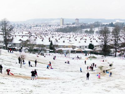 A snowy scene in Bristol, with families playing in a park