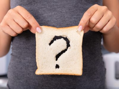 A woman holds a slice of bread with a question mark cut out of it